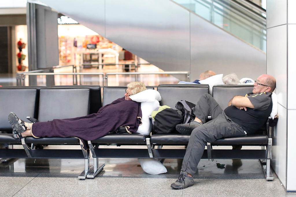 . Air travelers sleep on the bench in the international terminal at San Francisco International Airport July 7, 2013. Air travel continues to be heavily congested the day after Asiana Airlines flight 214 with 307 people on board crashed and burst into flames as it lands on the runway after a flight from Seoul, killing two people and sending more than 180 to local hospitals. REUTERS/Stephen Lam