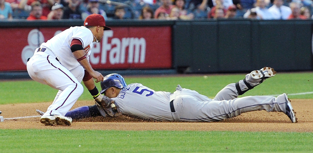 . Martin Prado #14 of the Arizona Diamondbacks tags out Carlos Gonzalez #5 of the Colorado Rockies at third base in the first inning at Chase Field on April 28, 2014 in Phoenix, Arizona.  (Photo by Norm Hall/Getty Images)