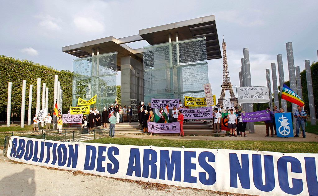 ". Pacifist militants stage a commemorative demonstration at the Peace Wall in Paris, Tuesday Aug. 6, 2013, to mark the 68th anniversary of the atomic bombing of Hiroshima. The sign in the foreground reads ""Abolition of Nuclear Weapons.\"" (AP Photo/Remy de la Mauviniere)"