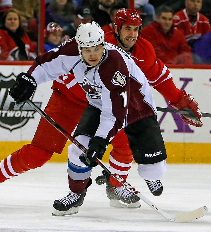 . Colorado Avalanche\'s John Mitchell (7) brings the puck down the ice as Carolina Hurricanes\' Jay Harrison (44) defends during the first period of an NHL hockey game in Raleigh, N.C., Tuesday, Nov. 12, 2013. (AP Photo/Karl B DeBlaker)