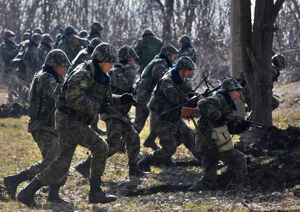 . Ukrainian border guards run to take their positions during training at a military camp in the village of Alekseyevka on the Ukrainian-Russian border, eastern Ukraine, Friday, March 21, 2014. Russian President Vladimir Putin has signed a resolution approved by parliament to annex Crimea. (AP Photo/Sergei Grits)
