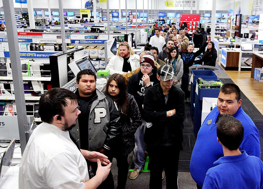 . This Thursday, Nov. 28, 2013 photo shows Best Buy employees standing in front of the line of patrons waiting to purchase a Xbox One console at the midnight doorbuster deal for Black Friday at the Best Buy located in Odessa, Texas. In the pre-dawn hours Friday, as some early-rising shoppers were heading into malls in search of Black Friday deals, others had been up shopping all night in stores that opened the evening of Thanksgiving or at 12:01 a.m. Friday. (AP Photo/Odessa American, Edyta Blaszczyk)