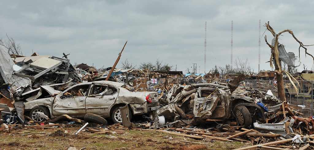. Damaged cars are seen near the tornado affected Plaza Towers Elementary School on May 26, 2013 in Moore, Oklahoma.  US President Barack Obama offered solace and support to residents of Oklahoma on Sunday as they rebuild their shattered lives after a monster tornado killed 24 people.      MANDEL NGAN/AFP/Getty Images