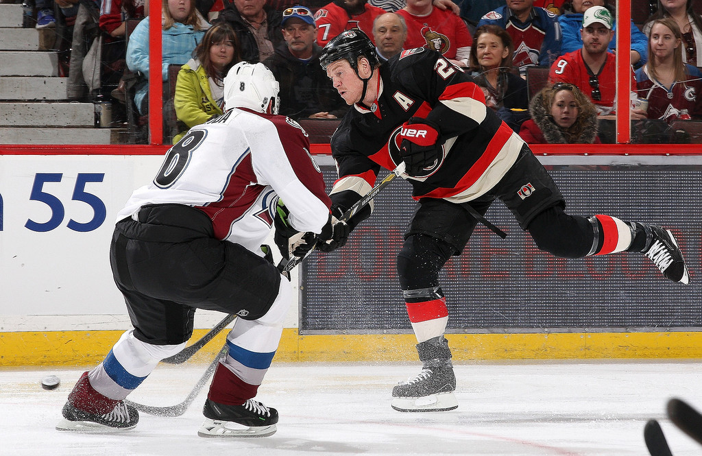 . Chris Neil #25 of the Ottawa Senators shoots the puck against Jan Hejda #8 of the Colorado Avalanche during an NHL game at Canadian Tire Centre on March 16, 2014 in Ottawa, Ontario, Canada.  (Photo by Jana Chytilova/Freestyle Photography/Getty Images)