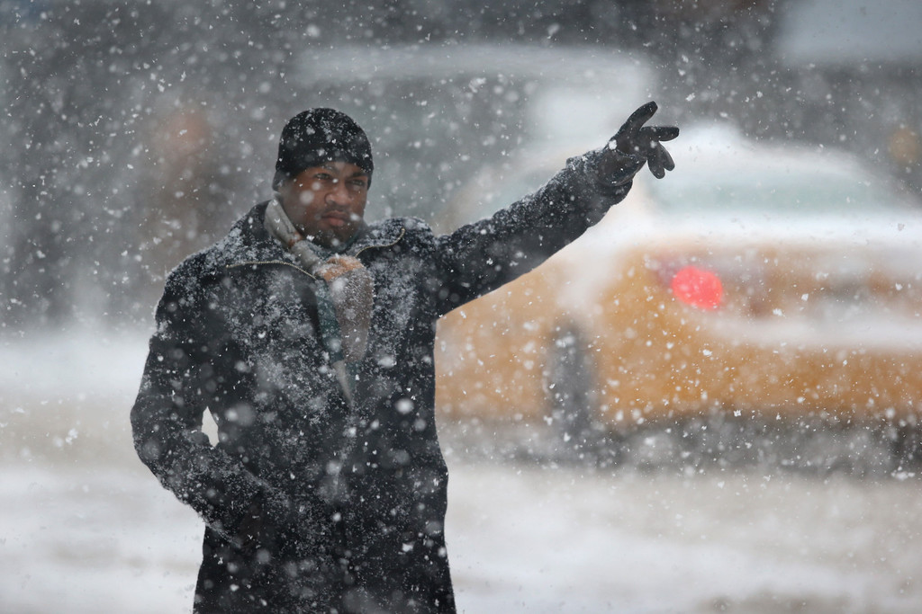 . A man hails a taxi in the snow on February 13, 2014 in New York City. Heavy snow and high winds made for a hard morning commute in the city.  (Photo by John Moore/Getty Images)