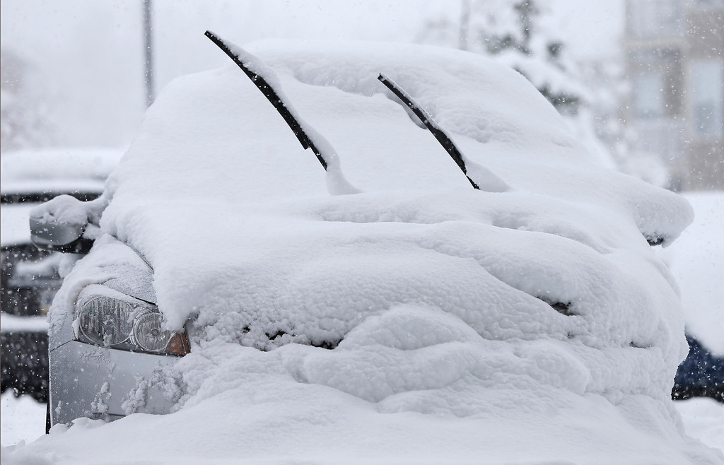 . A car is covered in snow Sunday, Jan. 5, 2014, in Zionsville, Ind. Snow that began in parts of Indiana Saturday night picked up intensity after dawn Sunday with several inches of snow on the ground by midmorning and more on the way. (AP Photo/Darron Cummings)