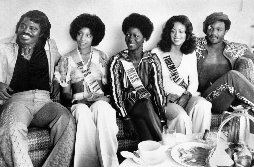 . World heavyweight champion George Foreman, right, relaxes with friends at a Zaire hotel, Sept. 20, 1974. At left is singer James Brown. The women, who did promotional work for the Foreman-Muhammad Ali fight, are, from left, Veronica Porche, Vickie King and Trina Booker, all from Los Angeles. (AP Photo/Horst Faas)