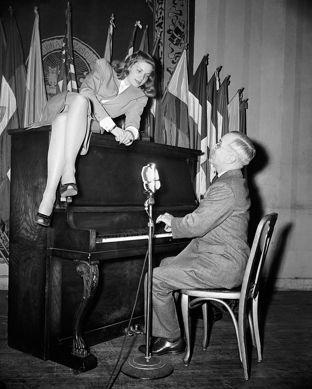 . FILE - In this Feb. 10, 1945 file photo, Vice President Harry S. Truman plays the piano as actress Lauren Bacall lies on top of it during her appearance at the National Press Club canteen in Washington. Bacall, the sultry-voiced actress and Humphrey Bogartís partner off and on the screen, died Tuesday, Aug. 12, 2014 in New York. She was 89. (AP Photo, File)