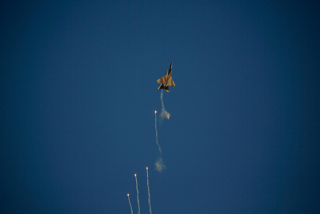 . An Israeli Air Force fighter jet releases flares during an aerobatic display at a graduation ceremony for new pilots in the Hatzerim air force base near the city of Beersheba, southern Israel, Thursday, Dec. 26, 2013. (AP Photo/Ariel Schalit)