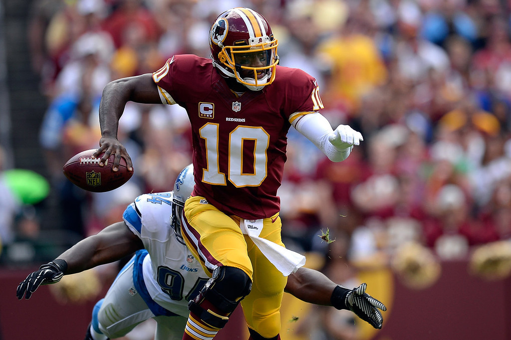 . Robert Griffin III #10 of the Washington Redskins scrambles with the ball as he avoids the tackle of Ezekiel Ansah #94 of the Detroit Lions in the first half during a game at FedExField on September 22, 2013 in Landover, Maryland.  (Photo by Patrick McDermott/Getty Images)