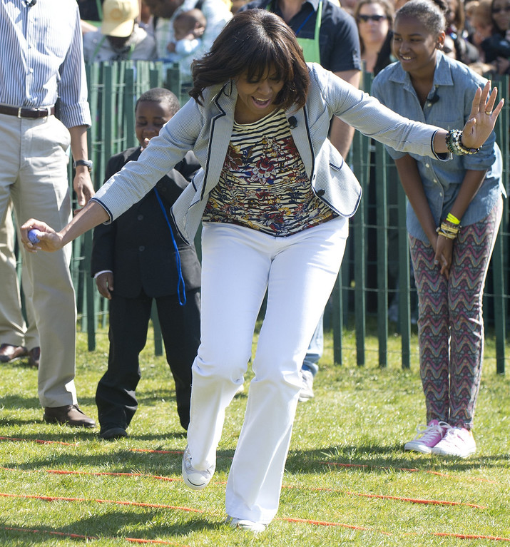 . US First Lady Michelle Obama picks up errant Easter eggs during the White House Easter Egg Roll on the South Lawn of the White House in Washington, DC, April 1, 2013. US President Barack Obama hosts the annual event, featuring live music, sports courts, cooking stations, storytelling and Easter egg rolling. AFP PHOTO / Saul LOEB/AFP/Getty Images