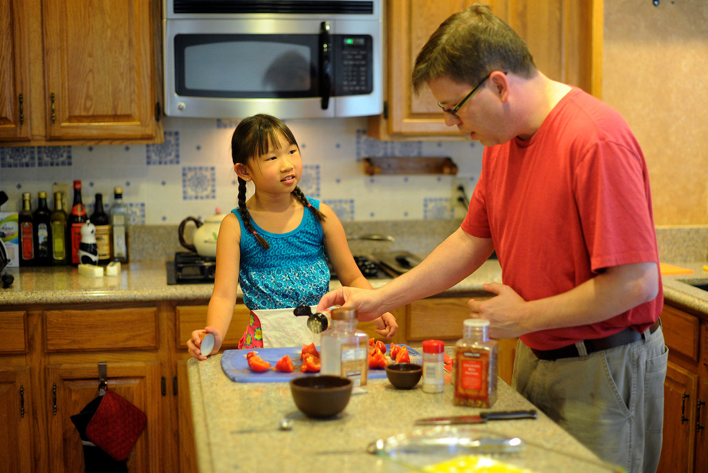 . WESTMINSTER, CO. -  JULY 5: Summer Love Series. The Ericksen family gathers at their Westminster home of their evening meal  on Friday, July 5, 2013. Christopher, right, cooks dinner with the help of daughter Eva, 9.  (Photo By Cyrus McCrimmon/The Denver Post)