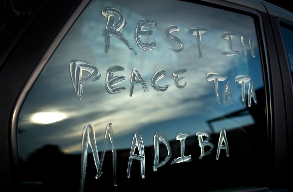 ". A message using Nelson Mandela\'s clan name ""Madiba\"" and a term of affection \""Tata\"" meaning \""father\"", is scrawled on the window of a car parked in the street outside Mandela\'s old house in Soweto, Johannesburg, South Africa Friday, Dec. 6, 2013. Flags were lowered to half-staff and people in black townships, in upscale mostly white suburbs and in South Africa\'s vast rural grasslands commemorated Nelson Mandela with song, tears and prayers on Friday while pledging to adhere to the values of unity and democracy that he embodied. (AP Photo/Ben Curtis)"