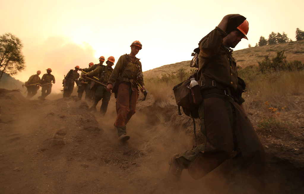 . Members of the Idaho City Hotshots walk along a dozer line made to protect homes from the more than 90,000-acre Elk Complex Fire near Pine, Idaho. on Monday, Aug.12, 2013. (AP Photo/Times-News, Ashley Smith)