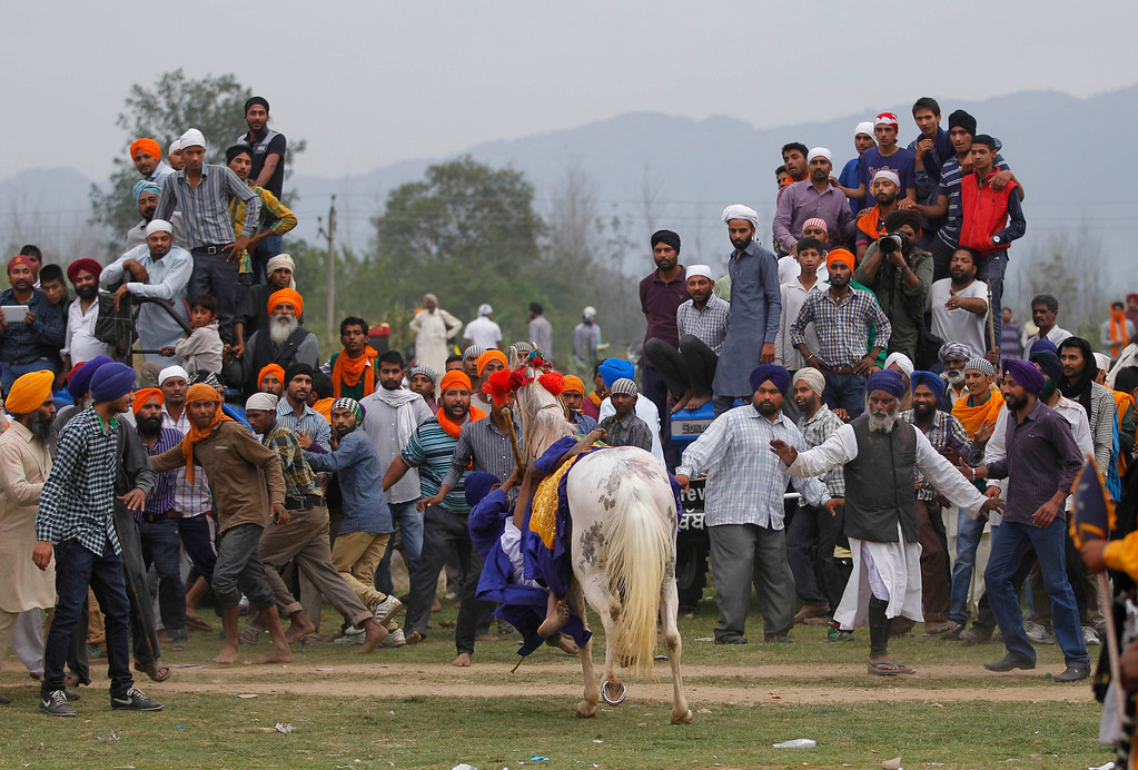 . A Nihang or Sikh warrior loses control of his horse during a display of horse riding skills at the annual fair of \'Hola Mohalla\'  in Anandpur Sahib, in the northern Indian state of Punjab, Monday, March 17, 2014. Believers from various parts of northern India collect at the religious fair to celebrate the festival of Holi in a tradition set by the tenth Sikh guru Guru Gobind Singh in the seventeenth century. Nihangs, or Sikh warriors, display their martial skills and attire during the fair, believed to be maintained in the exact tradition as set by the Guru. (AP Photo/Altaf Qadri)