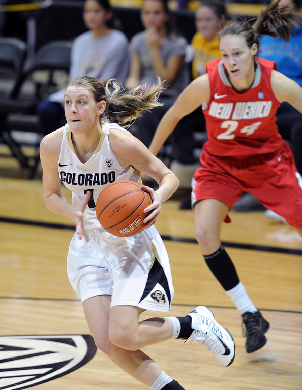 . Lexy Kresl of CU drives past Caroline Durbin of New Mexico on Saturday. Cliff Grassmick / December 29, 2012