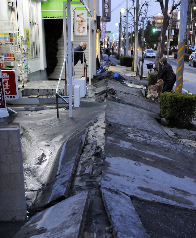 . A shop owner chats with a neighbour as the pedestrian road has collapsed in the massive 8.9-magnitude earthquake in Urayasu city, Chiba prefecture on March 11, 2011.  The earthquake shook Japan, unleashing powerful tsunamis that sent ships crashing into the shore and carried cars through the streets of coastal towns. (TOSHIFUMI KITAMURA/AFP/Getty Images)