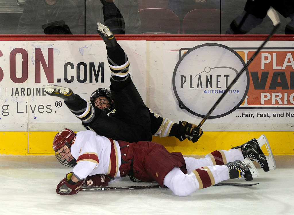 . DENVER, CO. - NOVEMBER 16: Western Michigan left wing Sam Mellor (28) took a tumble over Denver defenseman Josiah Didier (4) in the first period. The University of Denver hockey team hosted Western Michigan at Magness Arena Saturday night, November 16, 2013.  Photo By Karl Gehring/The Denver Post