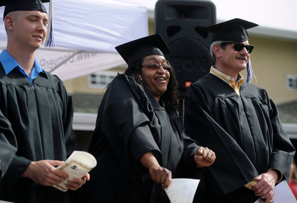 . Flanked by her fellow graduates Joshua Fuller, left, and Brad Barkey, right, Liberia Flowers does a little dance after she receives her certificate. (Photo By Kathryn Scott Osler/The Denver Post)
