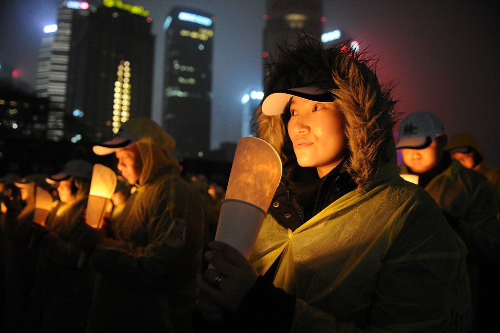". People light candles as they take part in an event to promote ""Earth Hour\"" in the financial district of Shanghai on March 23, 2013. Iconic landmarks and skylines were plunged into darkness as the \""Earth Hour\"" switch-off of lights around the world got under way including China\'s commercial hub of Shanghai to raise awareness of climate change.PETER PARKS/AFP/Getty Images"