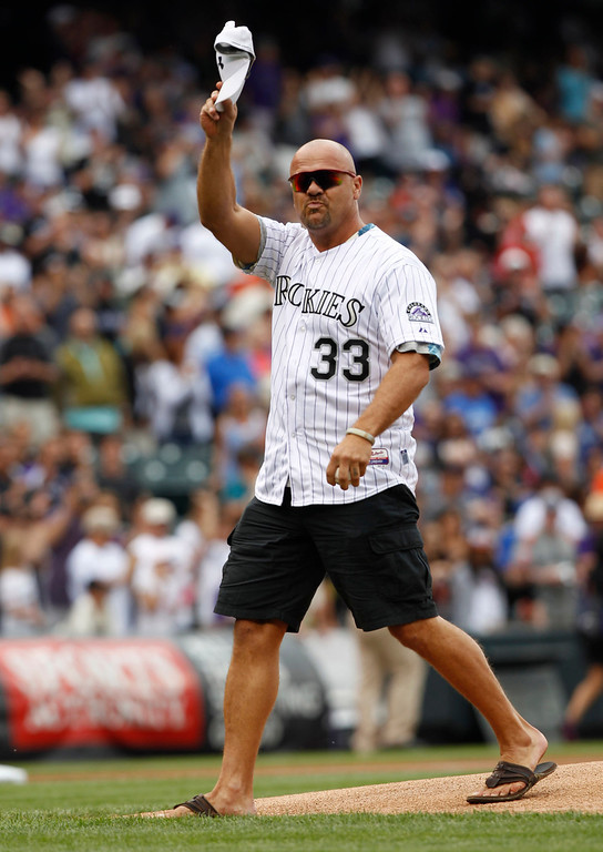 . Retired Colorado Rockies outfielder Larry Walker tips his cap to fans as he prepares to throw out the ceremonial first pitch to mark the issuance of his bobblehead before the Rockies host the San Francisco Giants in the first inning of a baseball game in Denver on Sunday, June 30, 2013. (AP Photo/David Zalubowski)