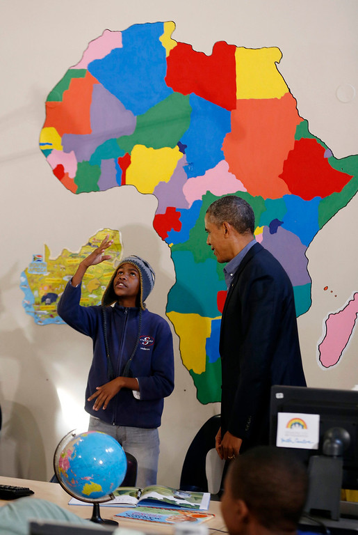 . U.S. President Barack Obama listens to young rapper Aviwe Ntongana, who calls himself \'Katmeister\', as he tours the Desmond Tutu HIV Foundation Youth Centre and takes part in a health event in Cape Town, South Africa on June 30, 2013.  REUTERS/Jason Reed