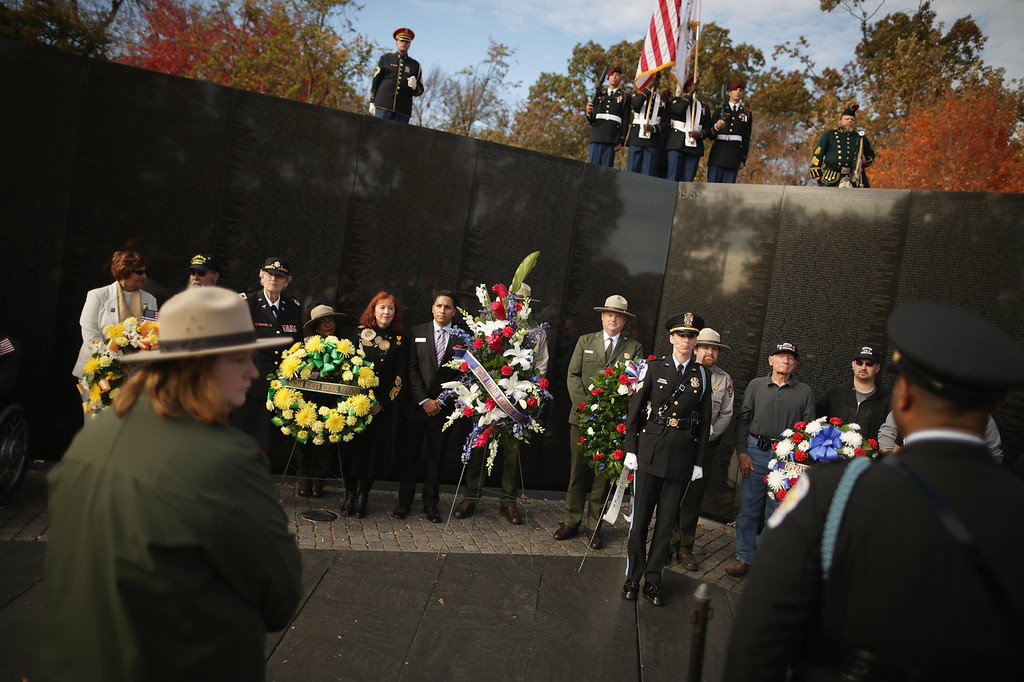 """. Veterans of the Vietnam War place wreaths at \""""The Wall\"""" during a Veterans Day event at the Vietnam Veterans Memorial on the National Mall November 11, 2013 in Washington, DC. Thousands of people gathered at \""""The Wall\"""" to pay respects and honor the men and women who served during the Vietnam War.  (Photo by Chip Somodevilla/Getty Images)"""