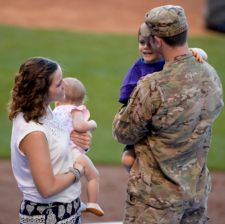 . Brian Hoffman, AFA, surprised his family with his homecoming from Afghanistan at the Colorado Rockies Arizona Diamondbacks game June 3, 2014 at Coors Field. Brian\'s son Kevin, 3, was all smiles in his arms as his wife Caitlin Hoffman holds their daughter 10-month-old daughter, Keira, as they stand on the Rockies dugout. (Photo by John Leyba/The Denver Post)