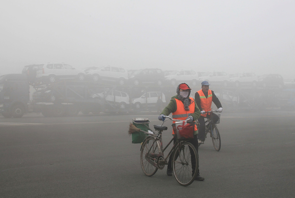 . Passerbys cycle past a truck waiting outside a closed toll booth as heavy smog spreads on a highway as vehicles are forced to wait due to heavy smog in Jilin, northeast China\'s Jilin province on October 22, 2013.   AFP PHOTOSTR/AFP/Getty Images