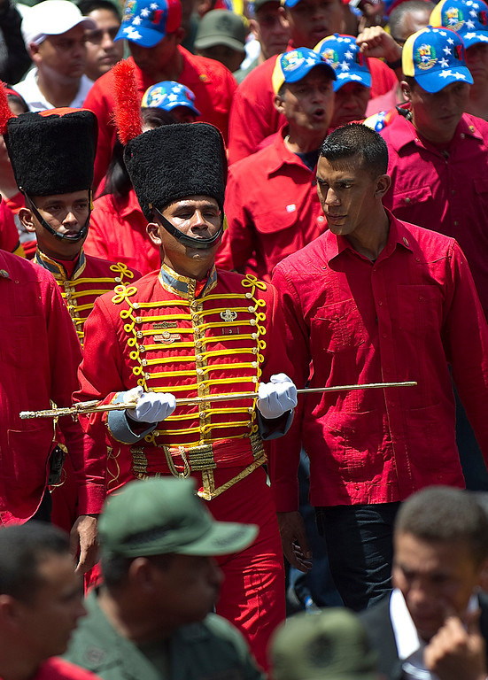 . A member of the Presidential Guard of Honor holds a replica of Simon Bolivar\'s sword while accompanying the hearse carrying the coffin of Venezuelan President Hugo Chavez on its way to the Military Academy, on March 6, 2013, in Caracas. AFP PHOTO/Juan BARRETO/AFP/Getty Images