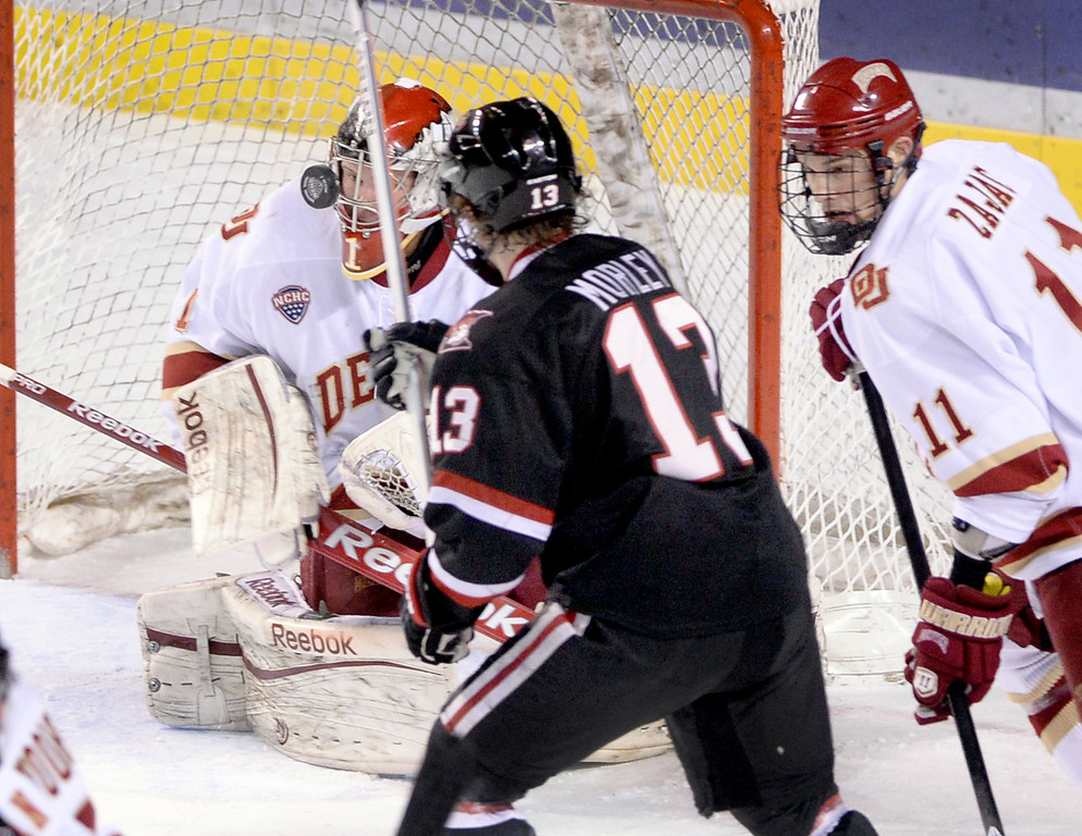 . DENVER, CO. - JANUARY 10: Huskies\' center David Morley (13) looked for a rebound after the puck bounced off Denver goaltender Sam Brittain in the first period. The University of Denver hockey team hosted St. Cloud State at Magness Arena Friday night, January 10, 2014. Photo By Karl Gehring/The Denver Post
