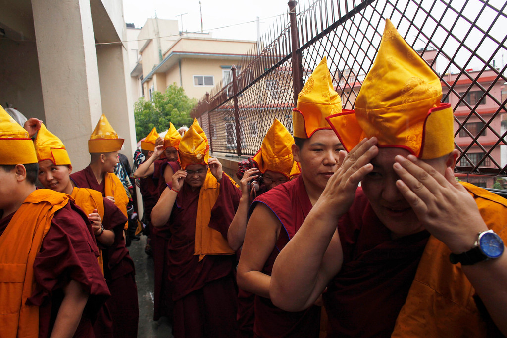 . Tibetan monks adjust their hats during celebrations to mark the birthday of their spiritual leader the Dalai Lama in Katmandu, Nepal, Saturday, July 6, 2013. The Tibetan leader turned 78 today. (AP Photo/Niranjan Shrestha)