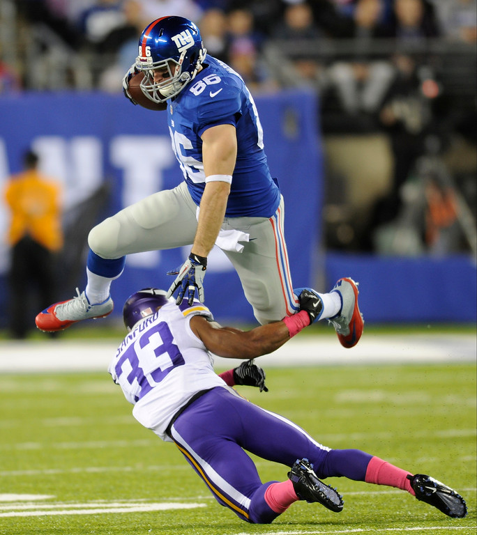 . New York Giants tight end Bear Pascoe (86) leaps over Minnesota Vikings\' Jamarca Sanford (33) during the first half of an NFL football game Monday, Oct. 21, 2013 in East Rutherford, N.J. (AP Photo/Bill Kostroun)