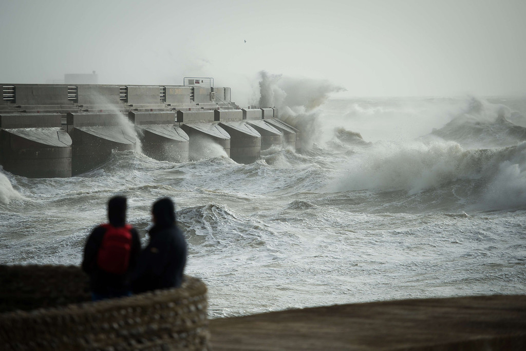 . People watch as large waves crash against the walls of Brighton Marina, southern England on October 27, 2013 as high winds pick up ahead of an expected storm. Britain was braced on October 27 for its worst storm in a decade, with heavy rain and winds of more than 80 miles (130 kilometres) an hour set to batter the south of the country.   LEON NEAL/AFP/Getty Images