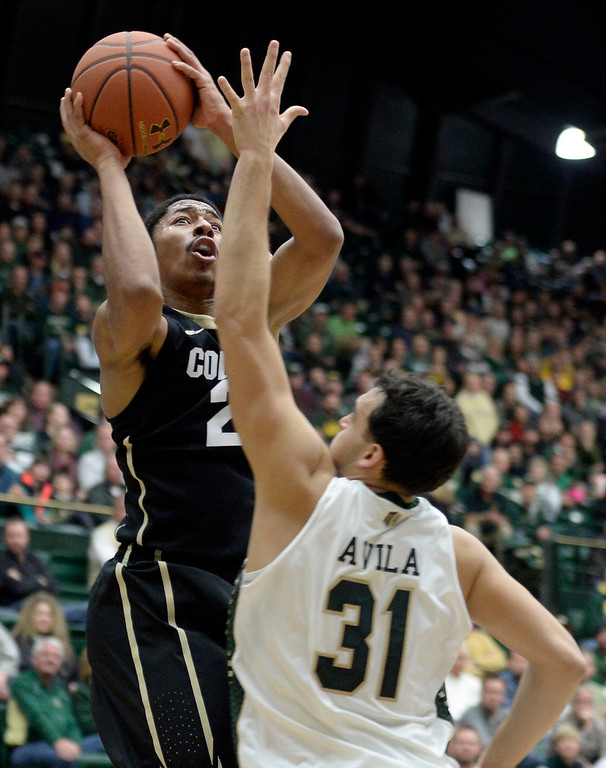 . University of Colorado\'s Spencer Dinwiddie takes a shot over J.J. Avila during an NCAA game against Colorado State University on Tuesday, Dec. 3, 2013, at the Moby Arena in Fort Collins.