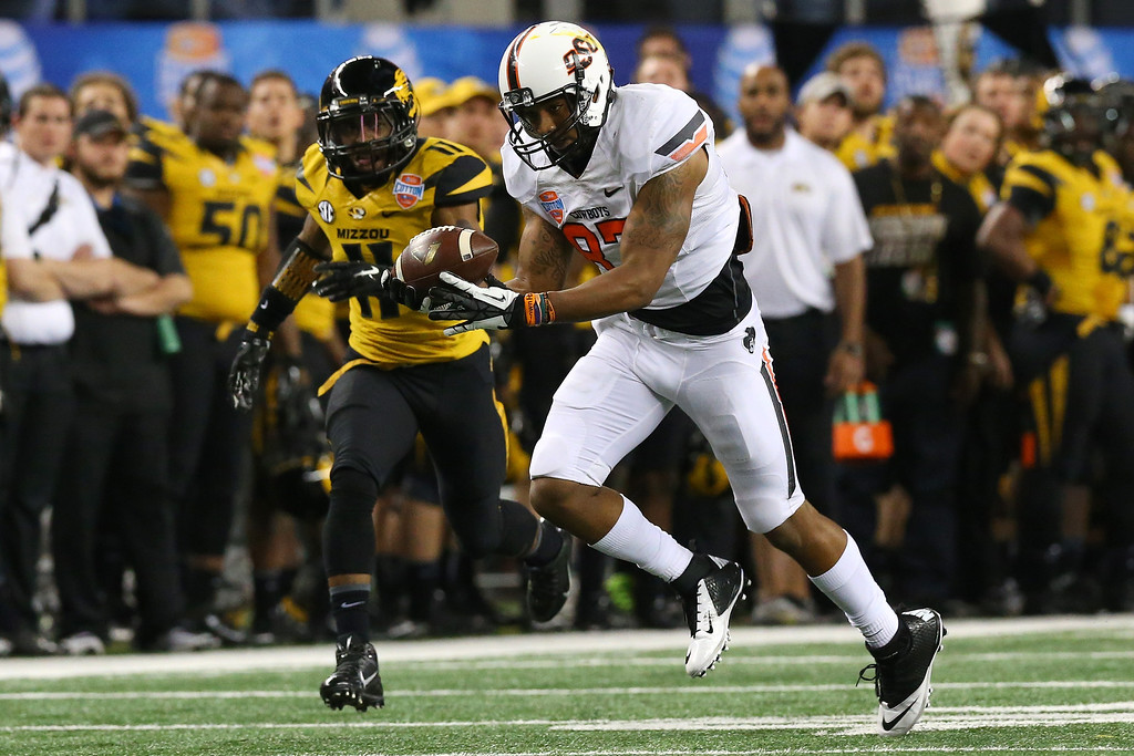 . ARLINGTON, TX - JANUARY 03:  Tracy Moore #87 of the Oklahoma State Cowboys makes a 41-yard catch against Aarion Penton #11 of the Missouri Tigers in the fourth quarter during the AT&T Cotton Bowl on January 3, 2014 in Arlington, Texas.  (Photo by Ronald Martinez/Getty Images)