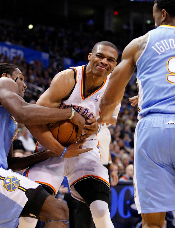 . Oklahoma City Thunder guard Russell Westbrook, center, gets caught between Denver Nuggets guard Andre Iguodala, right, and forward Kenneth Faried, left, on the way to the basket during the third quarter of an NBA basketball game in Oklahoma City, Wednesday, Jan. 16, 2013. Oklahoma City won 117-97. (AP Photo/Alonzo Adams)