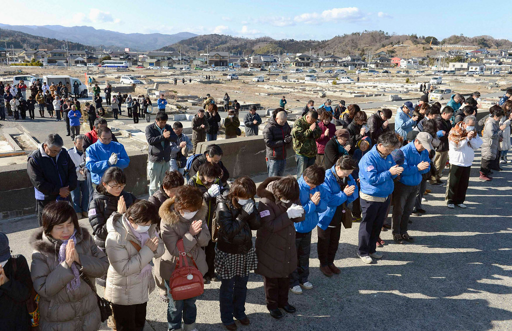. People observe a moment of silence facing the sea during a rally at 2:46 p.m. (0546 GMT), the time when the magnitude 9.0 earthquake struck off Japan\'s coast in 2011, in Iwaki, Fukushima prefecture, March 11, 2013 in this picture provided by Kyodo. Japan honoured the victims of its worst disaster since World War Two on Monday: the March 11, 2011 earthquake, tsunami and nuclear crisis that killed almost 19,000 people and stranded 315,000 evacuees, including refugees who fled radiation from the devastated Fukushima atomic plant. Mandatory Credit. REUTERS/Kyodo