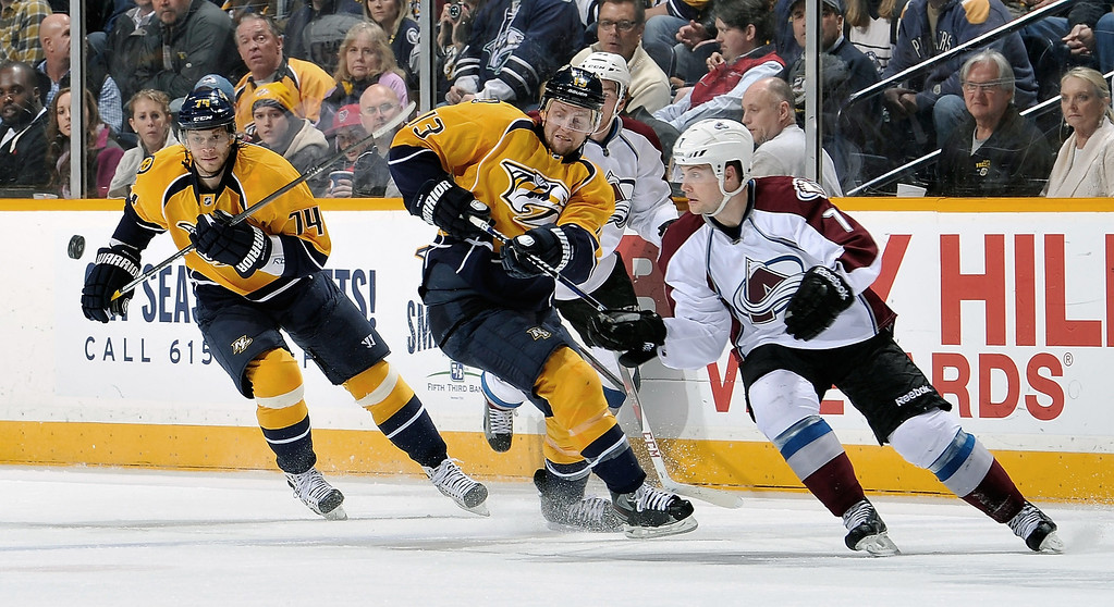 . Nick Spaling #13 and Sergei Kostitsyn #74 of the Nashville Predators and John Mitchell #7 of the Colorado Avalanche watch a bouncing puck at the Bridgestone Arena on April 2, 2013 in Nashville, Tennessee.  (Photo by Frederick Breedon/Getty Images)
