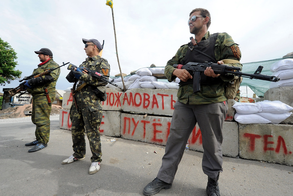 . Pro-Russian armed militants stand guard at a barricade which faces a position manned by Ukrainian army soldiers near the eastern Ukrainian city of Slavyansk, Donetsk region, on May 23, 2014. Russian President Vladimir Putin said today that the crisis in Ukraine had evolved into a full-scale civil war, blaming Washington for backing the overthrow of former president Viktor Yanukovych. AFP PHOTO / VIKTOR DRACHEV/AFP/Getty Images
