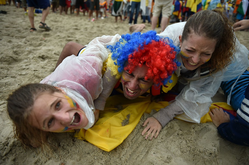 . Colombian fans react during Fanfesta\'s live projection of the 2014 FIFA World Cup Group C football match between Colombia and Ivory Coast at Copacabana beach in Rio de Janeiro on June 19, 2014.    AFP PHOTO/ YASUYOSHI  CHIBA/AFP/Getty Images