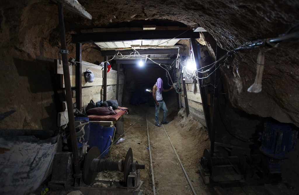 . In this Monday, Sept. 30, 2013 photo, a Palestinian man works in a tunnel in Rafah, on the border between Egypt and the southern Gaza Strip. Since the summer, Egypt�s military has tried to destroy or seal off most of the smuggling tunnels under the Gaza-Egypt border, a consequence of the heightened tensions between Cairo and the Hamas government in Gaza. The tunnels once employed thousands of young men in Gaza. By early September, with most tunnels closed, only few tunnel workers reported to their jobs for maintenance work. Some mask their faces with shirts to avoid identification while working, for fear of repercussions in case they were to travel to Egypt in the future. (AP Photo/Hatem Moussa)