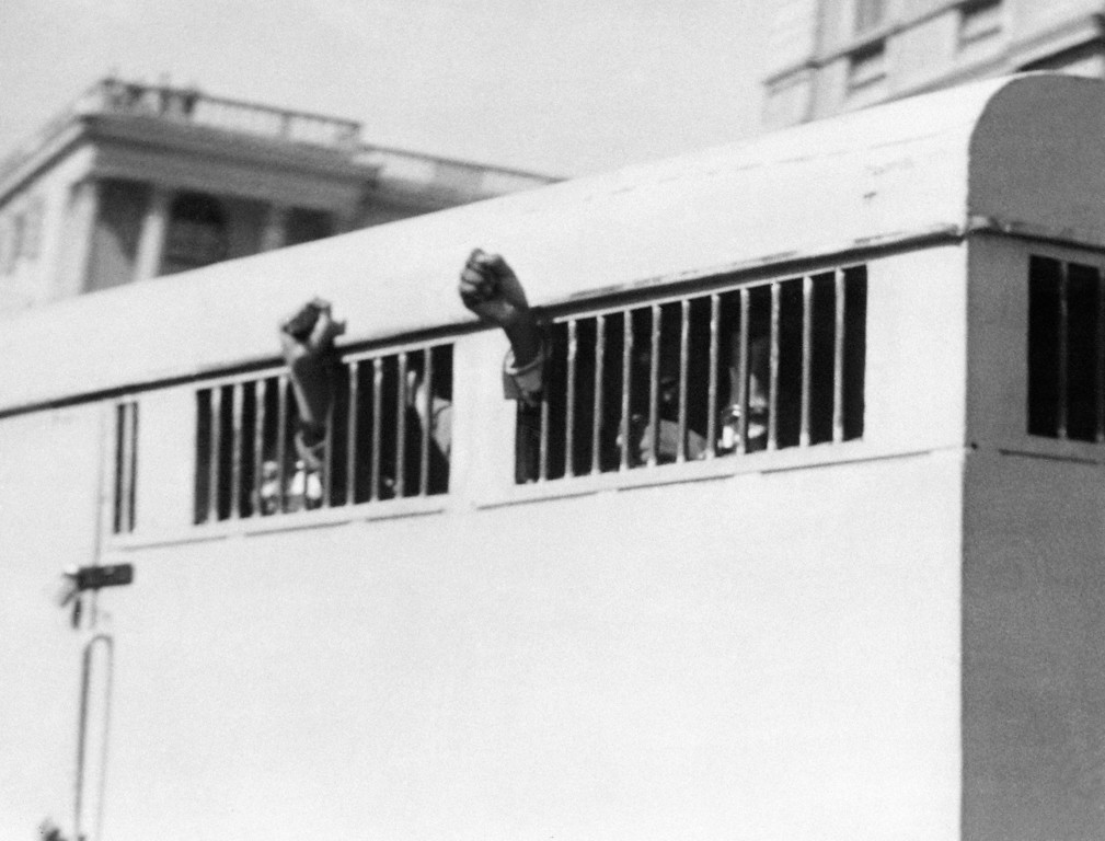 . Eight men, among them anti-apartheid leader and member of the African National Congress (ANC) Nelson Mandela, sentenced to life imprisonment in the Rivonia trial leave the Palace of Justice in Pretoria 16 June 1964 with their fists raised in defiance through the barred windows of the prison car. The eight men were accused of conspiracy, sabotage and treason. (OFF/AFP/Getty Images)