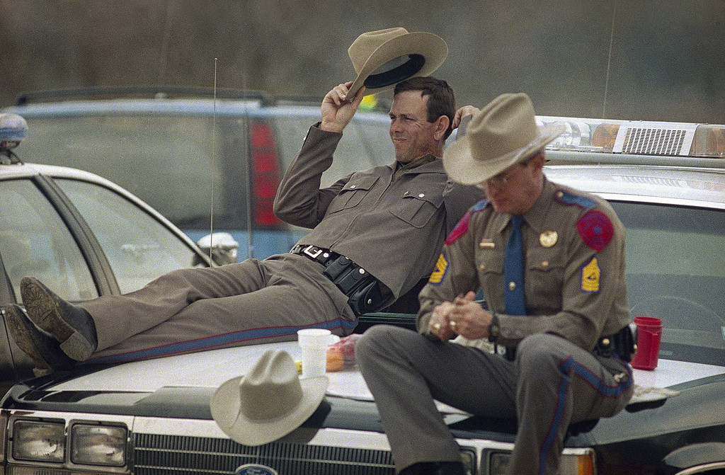 . Two Texas Department of Public Safety officers take it easy at a checkpoint near the Branch Davidian compound on Friday, March 20, 1993. Law officers have been in a standoff with David Koresh and his Branch Davidian followers since February 28 gunfights that ended with four Alcohol, Tobacco and Firearms agents and at least two cultists dead. (AP Photo/Ron Heflin)