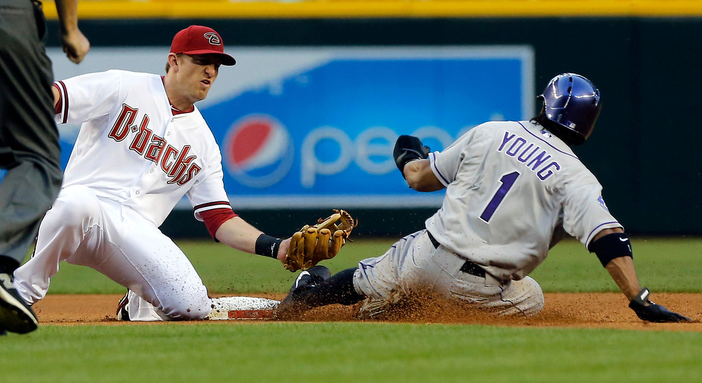 . Arizona Diamondbacks\' Cliff Pennington forces out Colorado Rockies\' Eric Young Jr. (1) on a double play during the first inning of a baseball game, Thursday, April 25, 2013, in Phoenix. (AP Photo/Matt York)