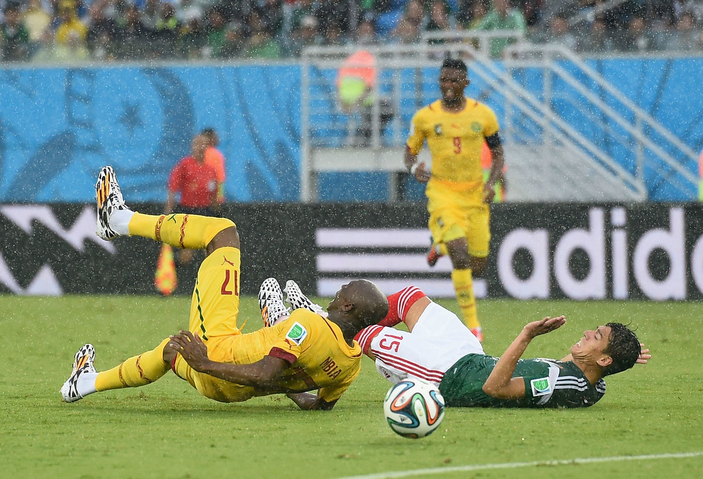 . Stephane Mbia of Cameroon collides with Hector Moreno of Mexico during the 2014 FIFA World Cup Brazil Group A match between Mexico and Cameroon at Estadio das Dunas on June 13, 2014 in Natal, Brazil. Moreno was given a yellow card.  (Photo by Matthias Hangst/Getty Images)