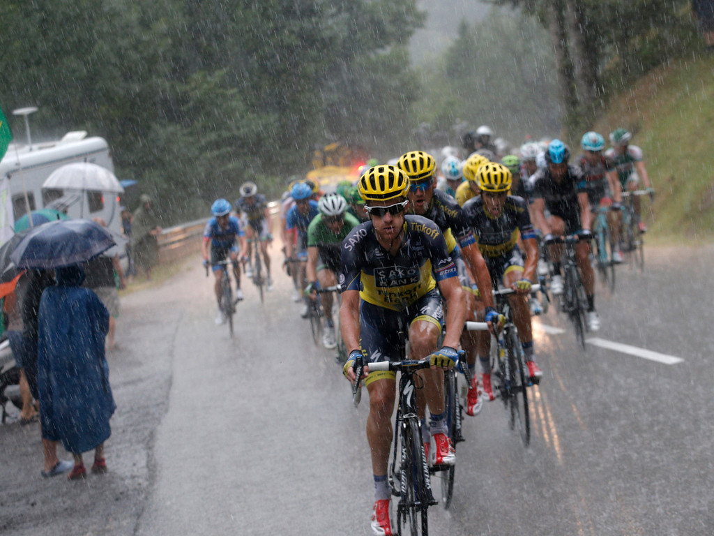 . The pack with Michael Rogers of Australia, front, Roman Kreuziger of the Czech Republic, in second position, and Spain\'s Alberto Contador in third position, rides in a downpour during the nineteenth stage of the Tour de France cycling race over 204.5 kilometers (127.8 miles) with start in in Bourg-d\'Oisans and finish in Le Grand-Bornand, France, Friday July 19 2013. (AP Photo/Christophe Ena)