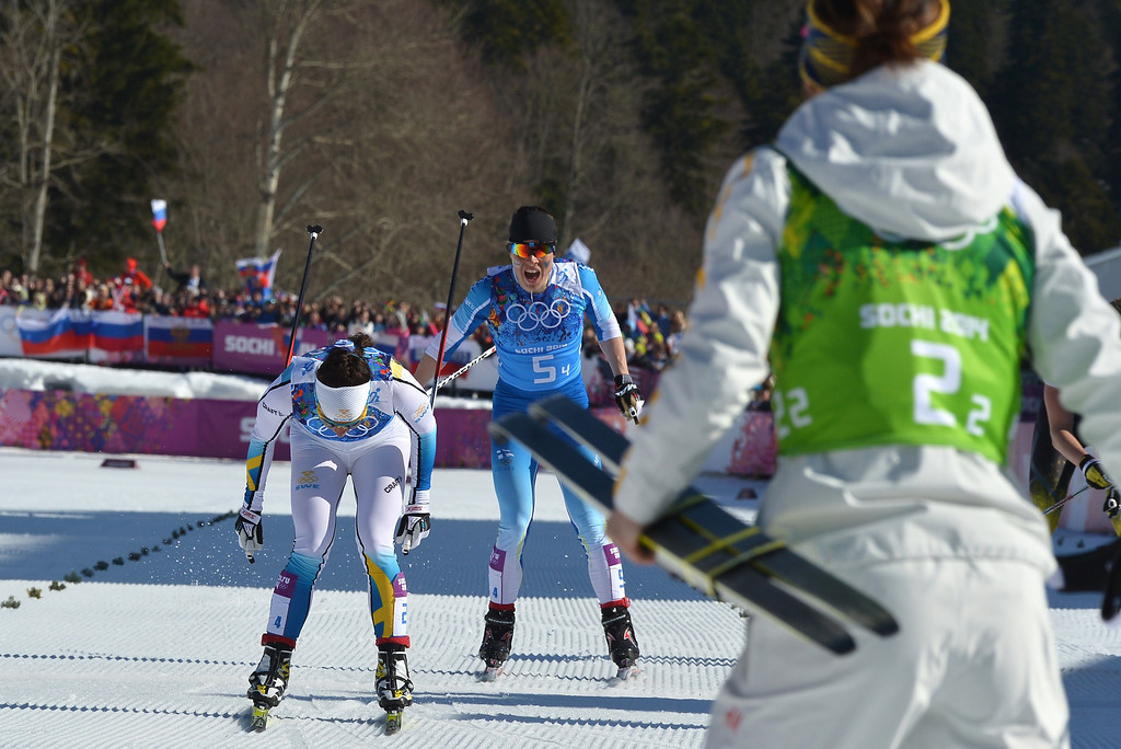 . Sweden\'s Charlotte Kalla (L) crosses the finish line to win Gold ahead of Finland\'s Krista Lahteenmaki (C) in the Women\'s Cross-Country Skiing 4x5km Relay at the Laura Cross-Country Ski and Biathlon Center during the Sochi Winter Olympics on February 15, 2014, in Rosa Khutor, near Sochi.        ALBERTO PIZZOLI/AFP/Getty Images