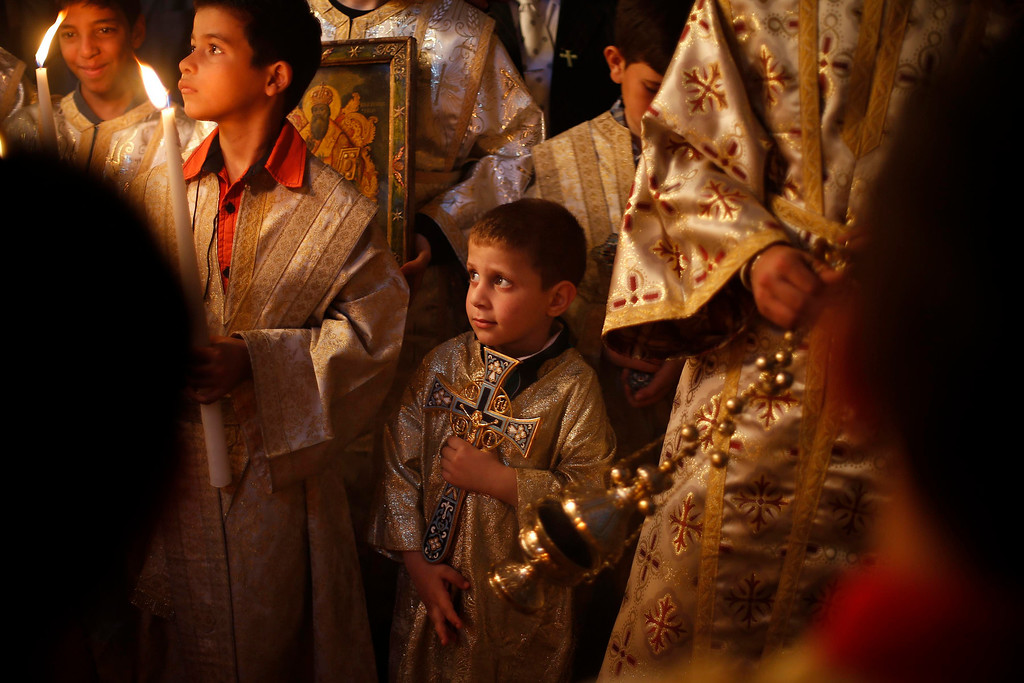 . A Palestinian Orthodox Christian boy holds a cross during Palm Sunday mass at the Saint Porfirios church in Gaza City April 28, 2013.  REUTERS/Suhaib Salem