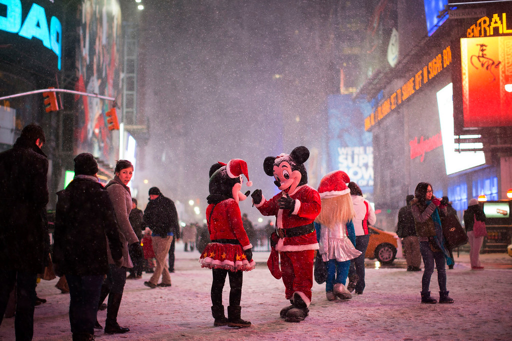 . Two people dressed as Disney characters talk under falling snow in Times Square, Thursday, Jan. 2, 2014, in New York. The storm is expected to bring snow, stiff winds and punishing cold into the Northeast. (AP Photo/John Minchillo)
